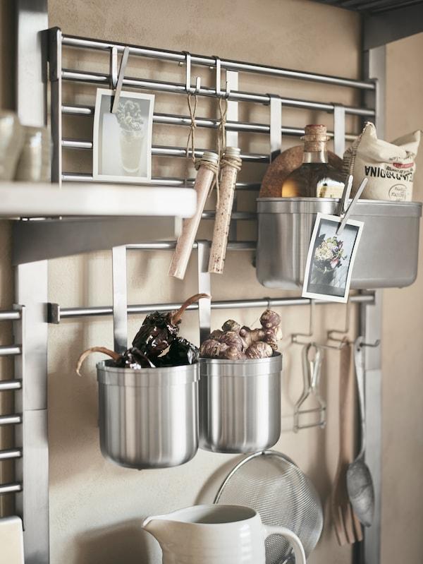 Kratka ścienna KUNGSFORS ze stali nierdzewnej z korzeniami imbiru i przyprawami w pojemnikach oraz przyborami kuchennymi zawieszonymi na haczykach.