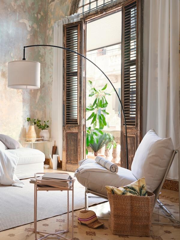 Sala com poltrona branca, ao lado, no chão uma cesta com uma almofada em cima e uma mesa de centro em frente com várias revistas.