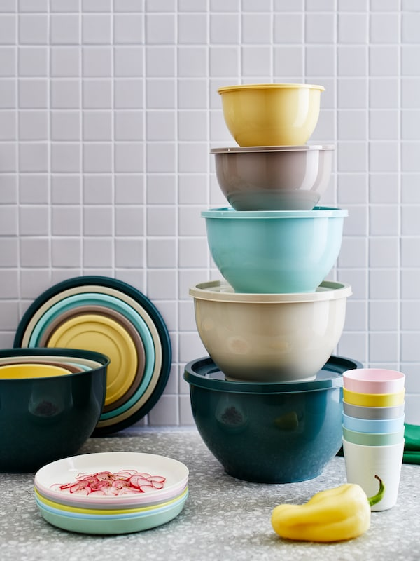 Kitchen countertop with stacked lidded bowls in mixed colours next to KALAS plates and mugs, also in mixed colours.