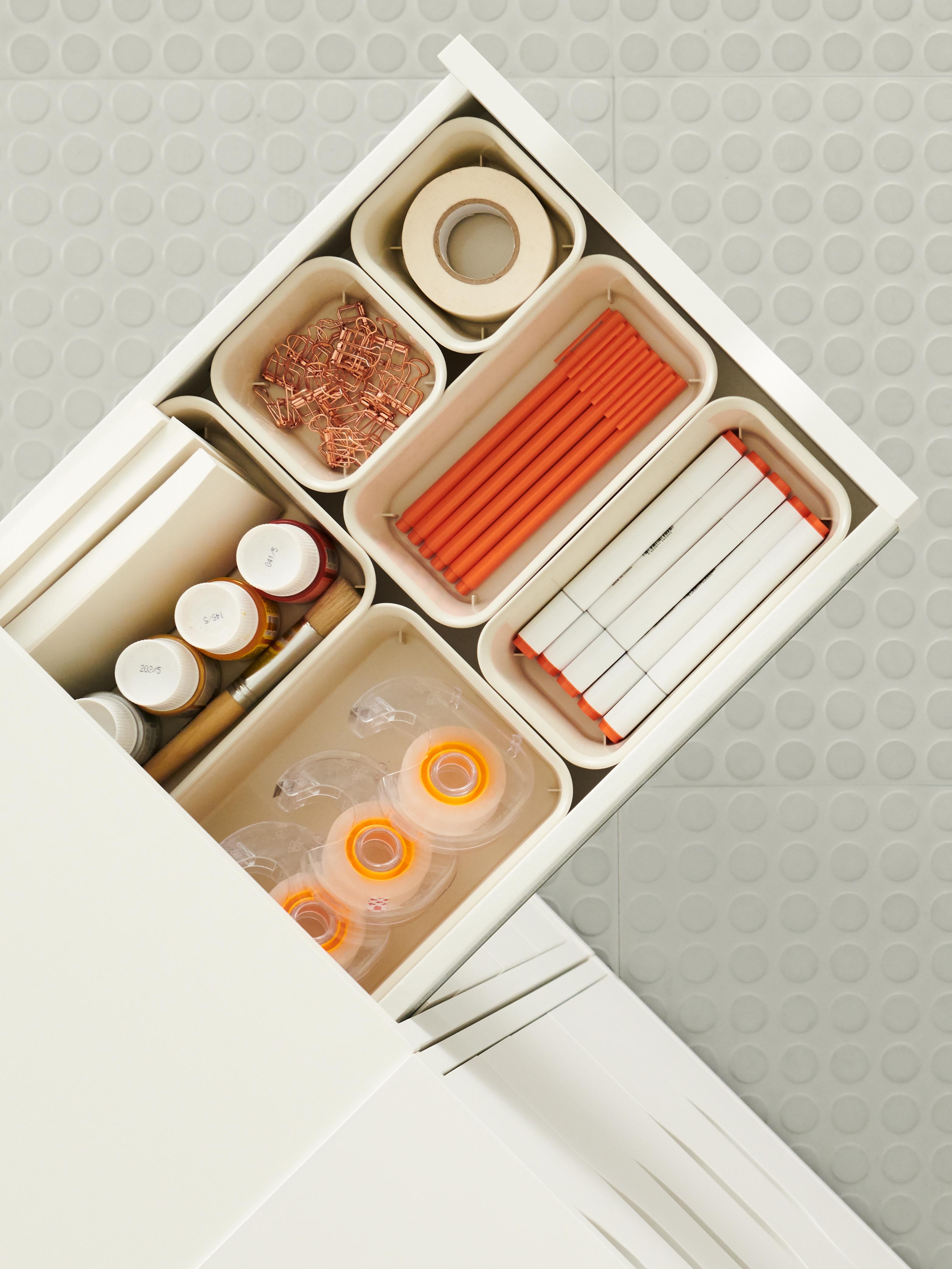 Eine Schublade, die aus einer weissen Einheit herausragt und verschiedene Organizer mit Klebeband, Stiften, Büroklammern usw. mit orangefarbenen Akzenten enthält.