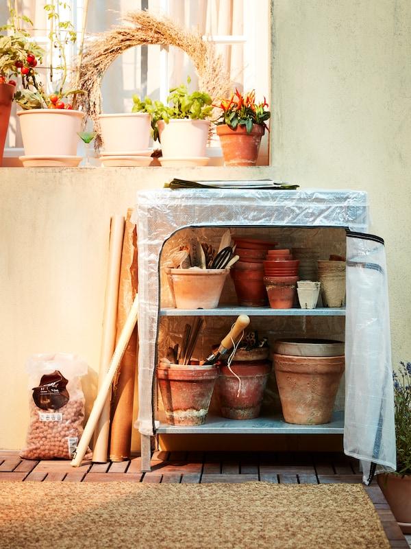 Ein Metallregal mit Abdeckung, u. a. mit gestapelten Terracottatöpfen und Gartenutensilien. Auf einer Fensterbank stehen Topfpflanzen.