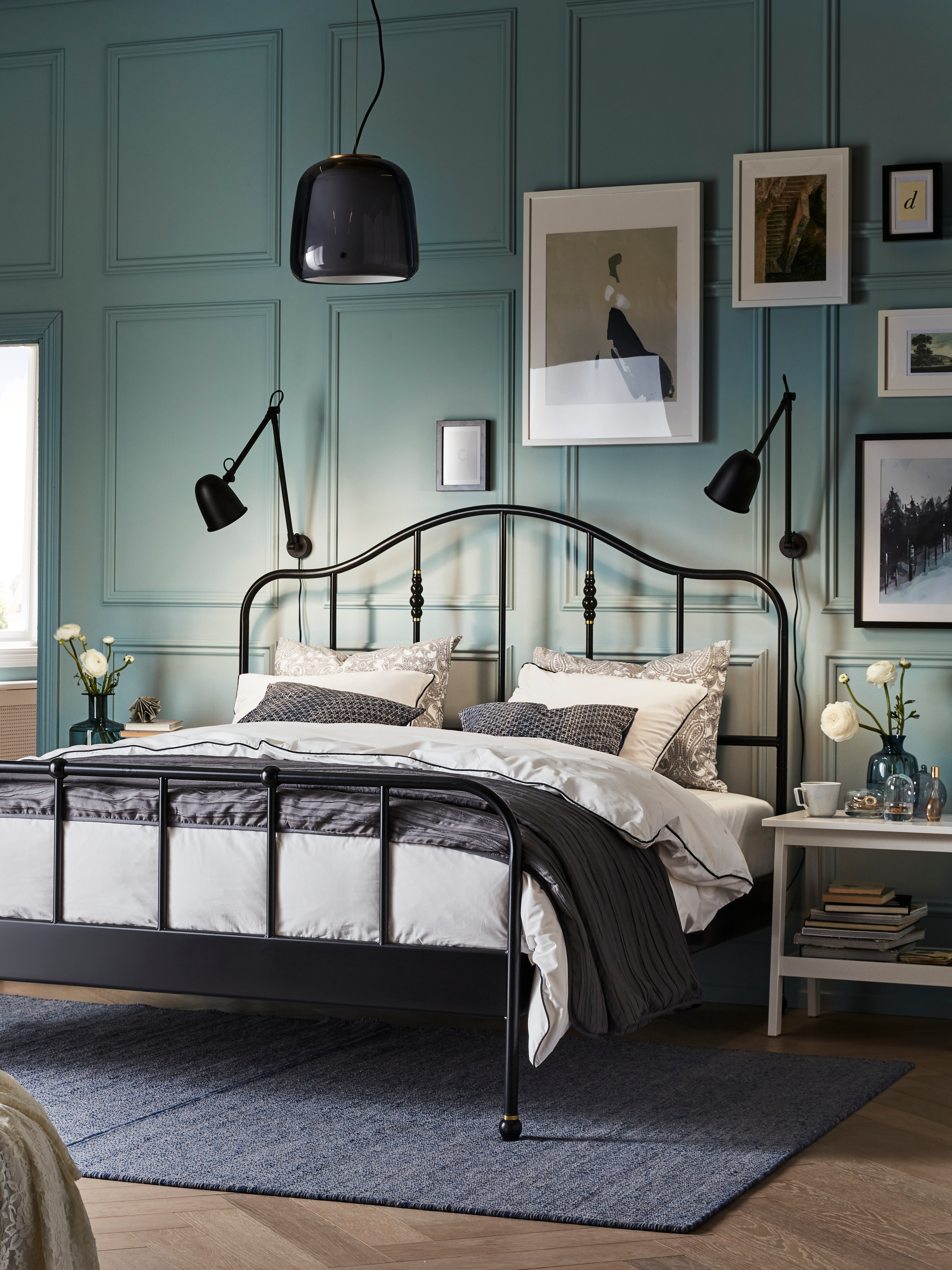 SAGSTUA black bed frame with grey bedspread under a grey glass and brass pendant lamp in a bedroom with a green wall.