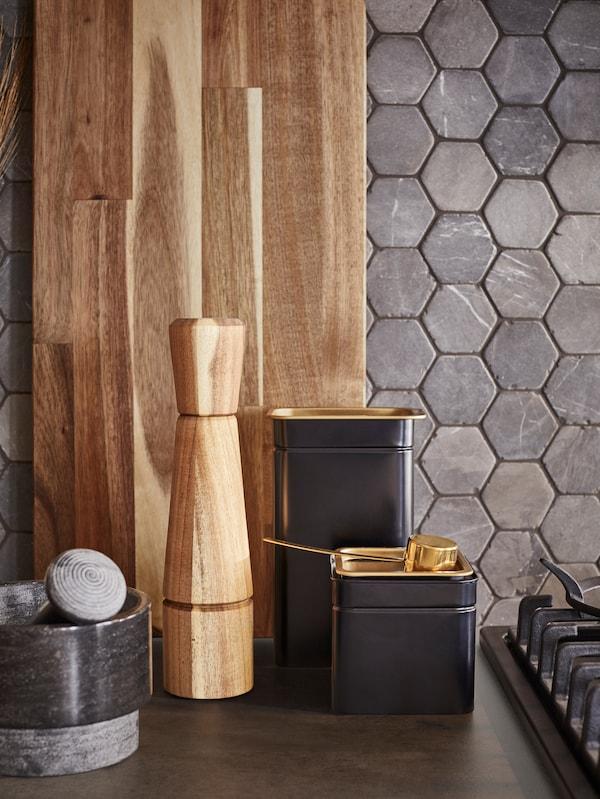 Un tagliere, un macinaspezie in legno d'acacia, due barattoli di caffè/tè e un pestello e mortaio nero su un piano di lavoro.