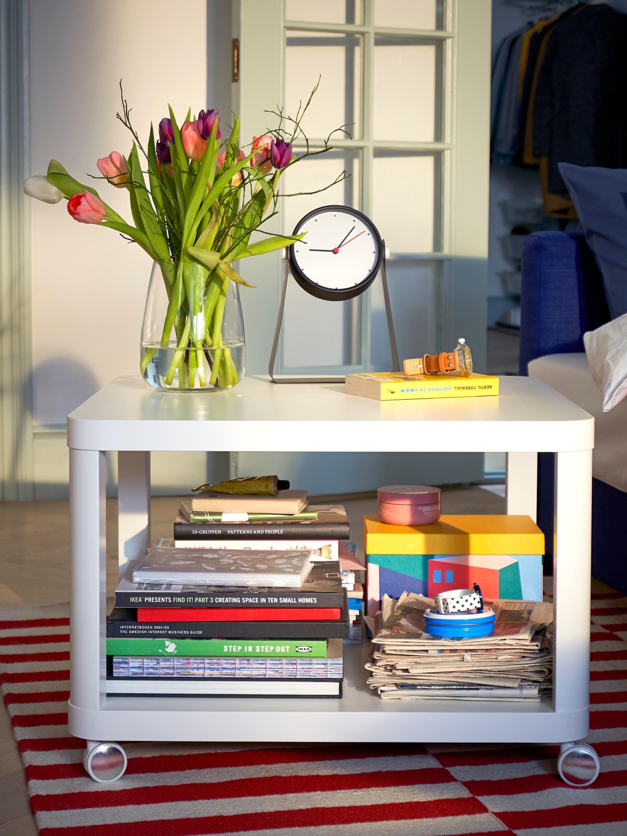 TINGBY beli pomoćni stočić na točkićima, s puno knjiga na donjem nivou i vazom s cvećem i satom na vrhu.