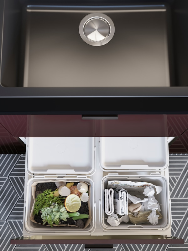 An open kitchen drawer with a light grey HÅLLBAR waste sorting solution containing food waste and paper for recycling.