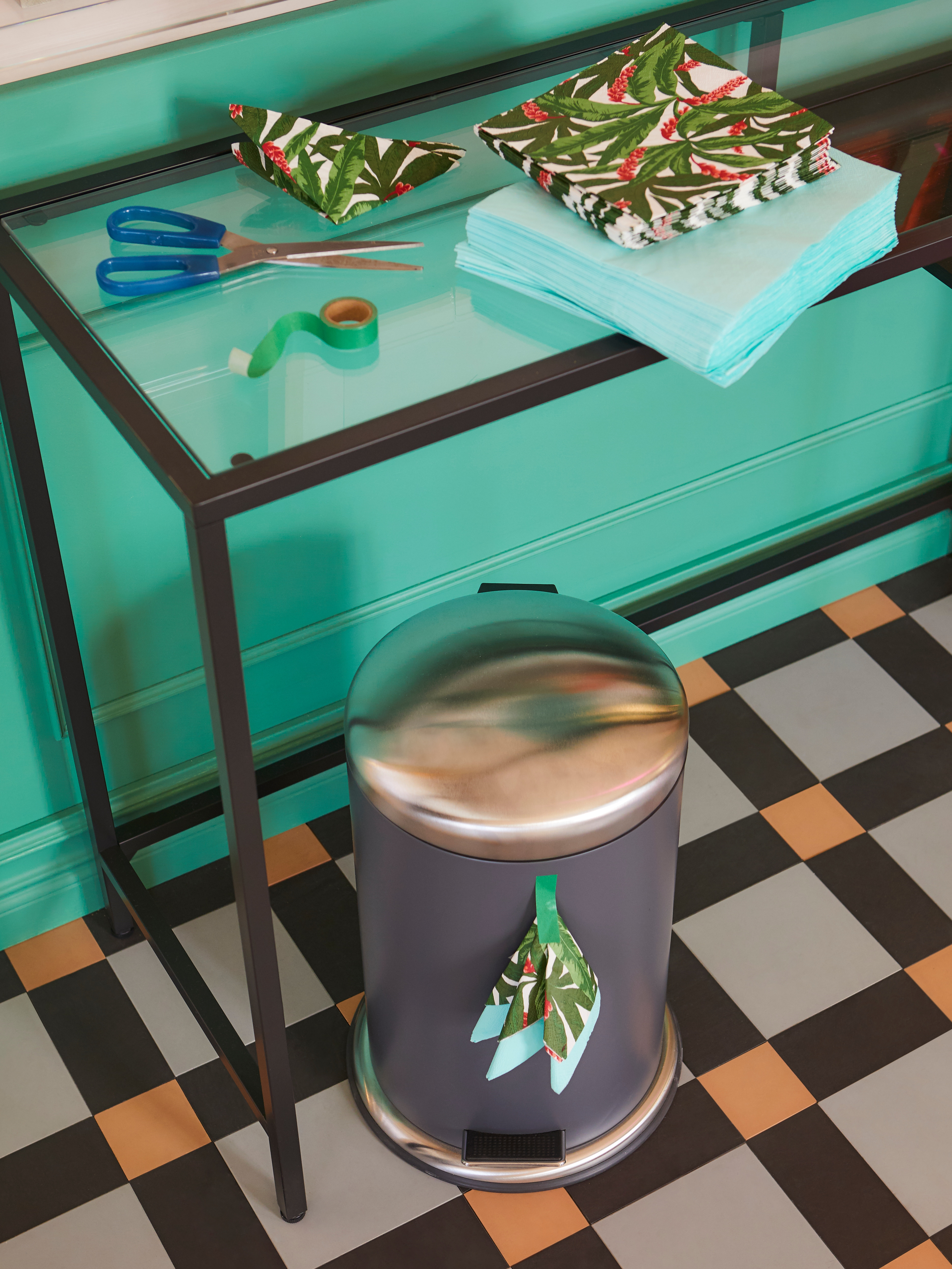 A black-brown/glass VITTSJÖ laptop table is  along a wall, holding piles of paper napkins. A pedal bin is below on the floor.