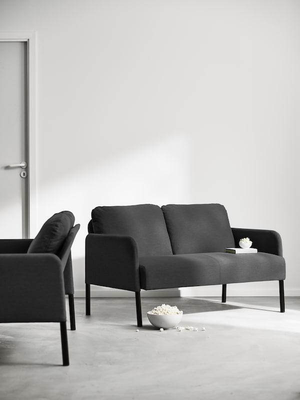 Dua sofa GLOSTAD dua tempat duduk berwarna biru menghadap satu sama lain di ruang yang terang. Semangkuk besar popcorn ada di lantai.