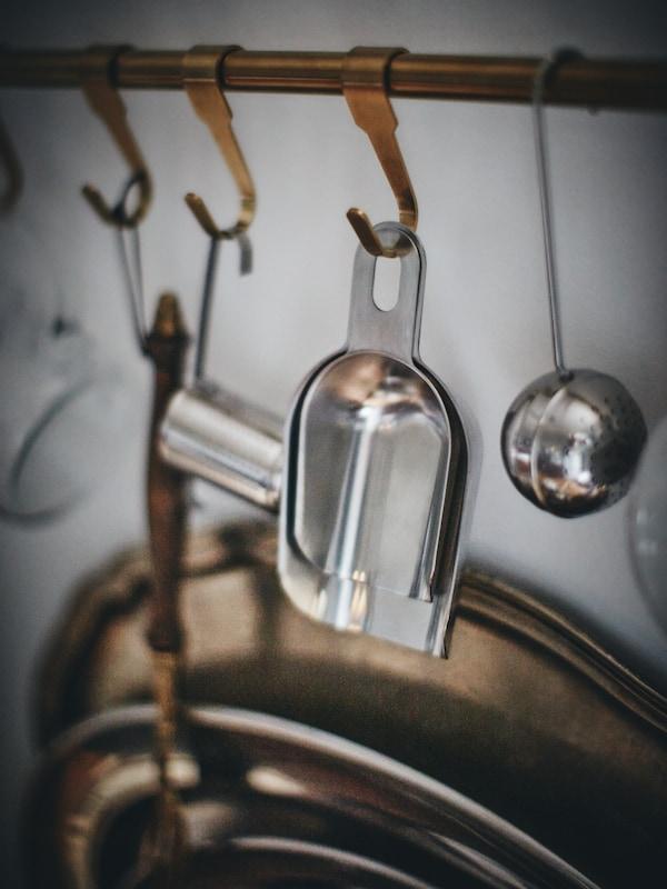 لقطة مقرّبة لسكة تعليق مطبخ تتدلى منها أواني من الستنلس ستيل.