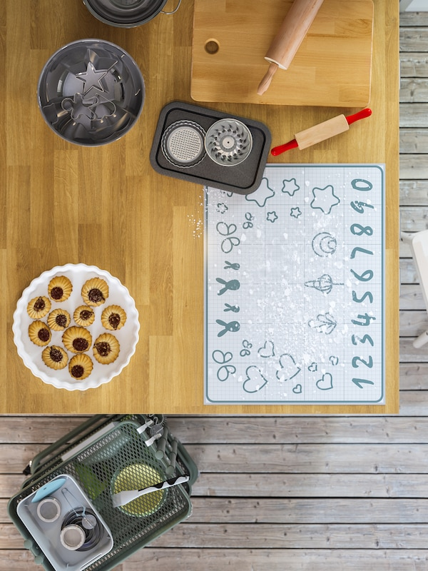 A wooden kitchen island with a baking mat to trace cookie shapes, cookies, cutting board and bakeware.