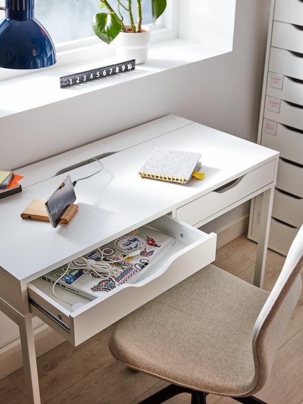 Scrivania bianca poco profonda con due cassetti. Un cassetto è aperto e all'interno ci sono un PC portatile decorato con adesivi e dei cavi per la ricarica.