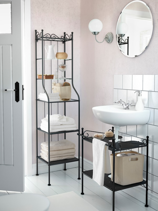 A bathroom in traditional style with a round mirror, FRIHULT lamp and a neatly decorated black RÖNNSKÄR shelving unit.