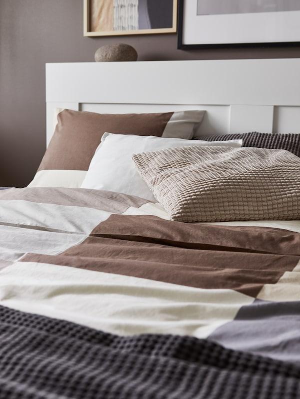 Katil berwarna putih dengan kepala katil, sarung kuilt dan sarung bantal bercorak warna coklat, alas berwarna kelabu dan kusyen berwarna putih, kelabu dan kuning air.
