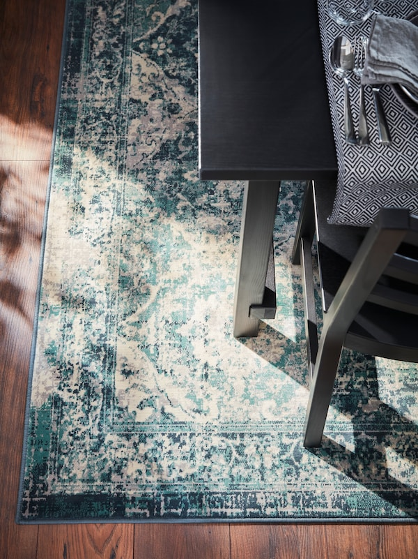 A rug with a design in green and white, with a table and chair on it, the table cloth has cutlery on it.