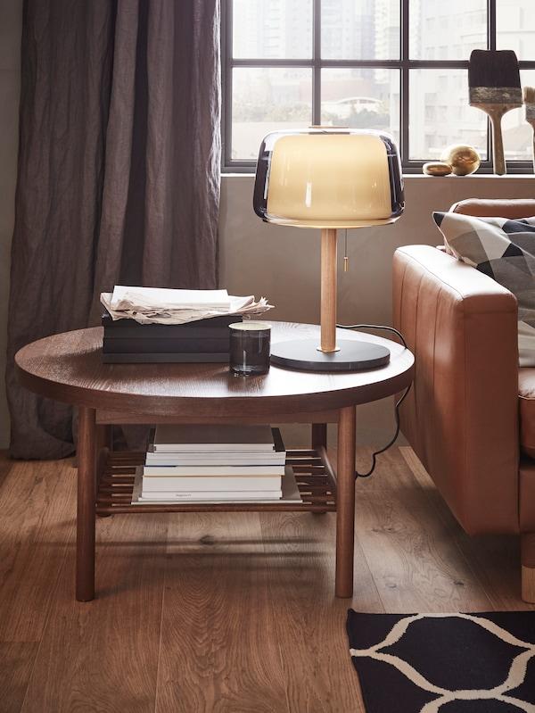 Der runde LISTERBY Couchtisch neben einem Sofa. Auf dem Tisch sind eine Leuchte und Papiere zu sehen.