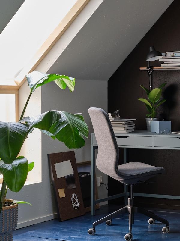 une pièce avec un bureau gris turquoisze, une chaise de bureau noire et des plantes