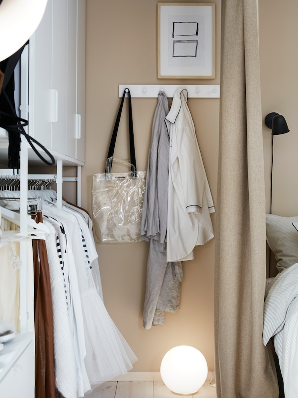 Clothes hang to get aired on a white LURT/GUBBARP rack with six knobs, mounted on the wall next to an open wardrobe.