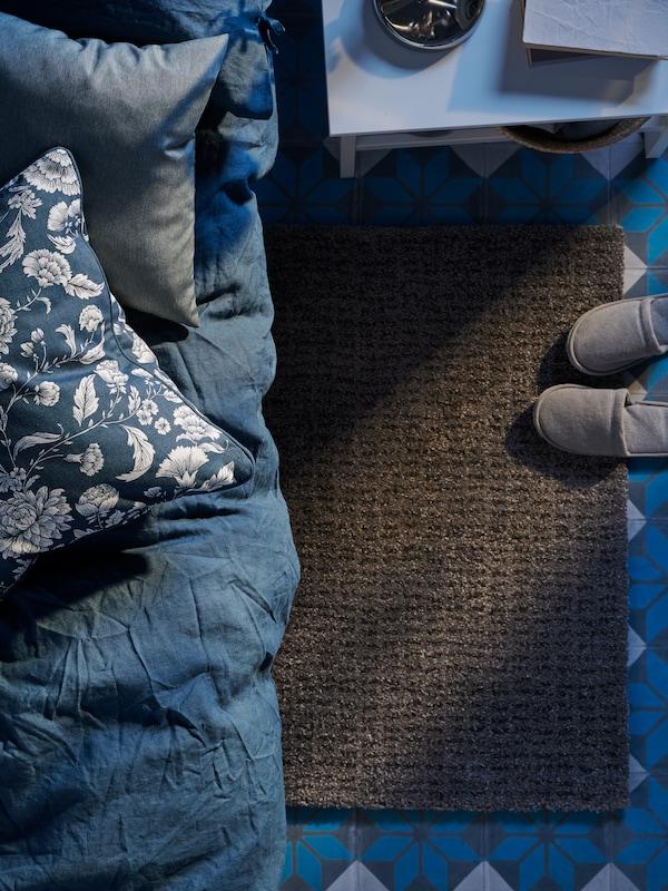 En ljusgrå LANGSTED matta ligger under en säng med ett blåvitt IDALINNEA kuddfodral och blå sängkläder.