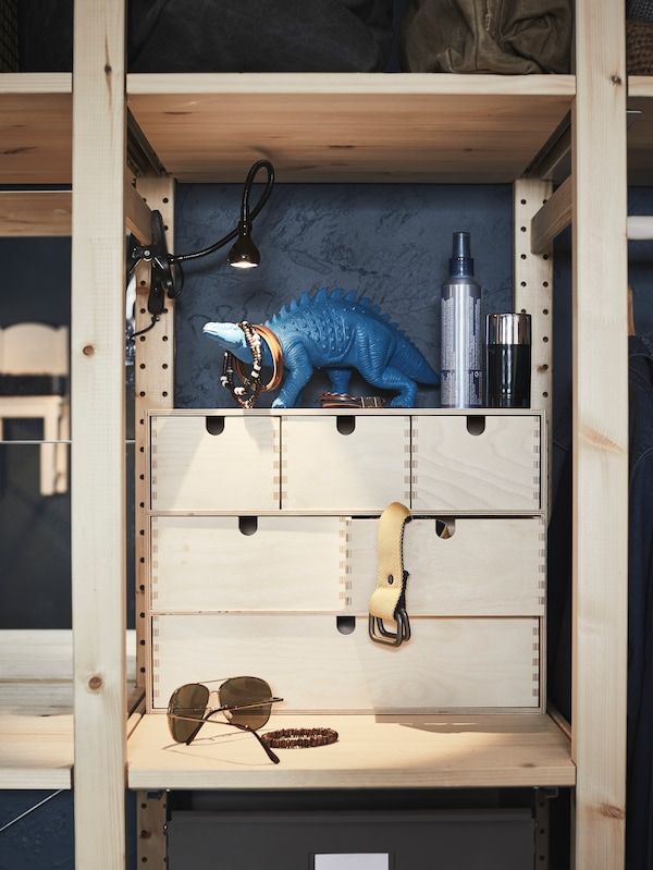A wooden MOPPE mini chest of drawers sits on a shelf in an IVAR storage combination with a JANSJÖ lamp shining on it.