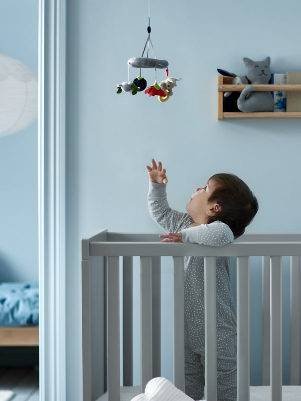 Na sivom SUNDVIK krevetiću za bebe stoji beba i poseže za mobilom, dok na zidnom rješenju za odlaganje u pozadini stoji plišana igračka.