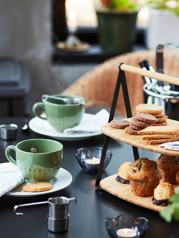 A close-up of a table with mugs, lit tealights and a FULLSPÄCKAD serving tray holding pastries on its two trays.
