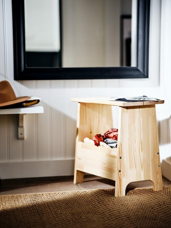 Un tabouret PERJOHAN en pin sur un tapis brun dans un espace ensoleillé à côté d'une étagère basse et devant un miroir TOFTBYN noir.