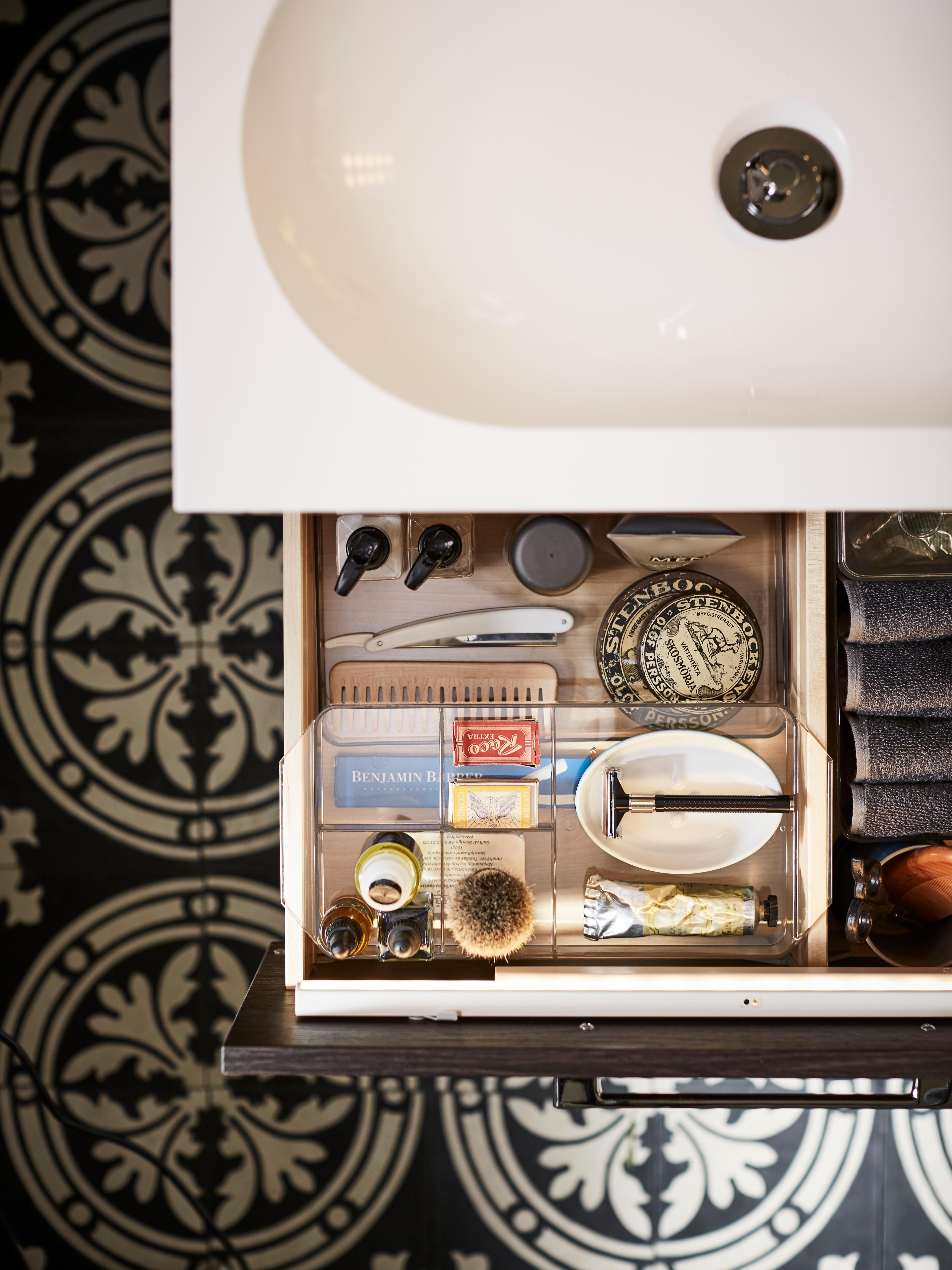 Un cassetto aperto, visto dall'alto, con una scatola a scomparti GODMORGON in plastica trasparente che contiene prodotti e accessori per la barba.