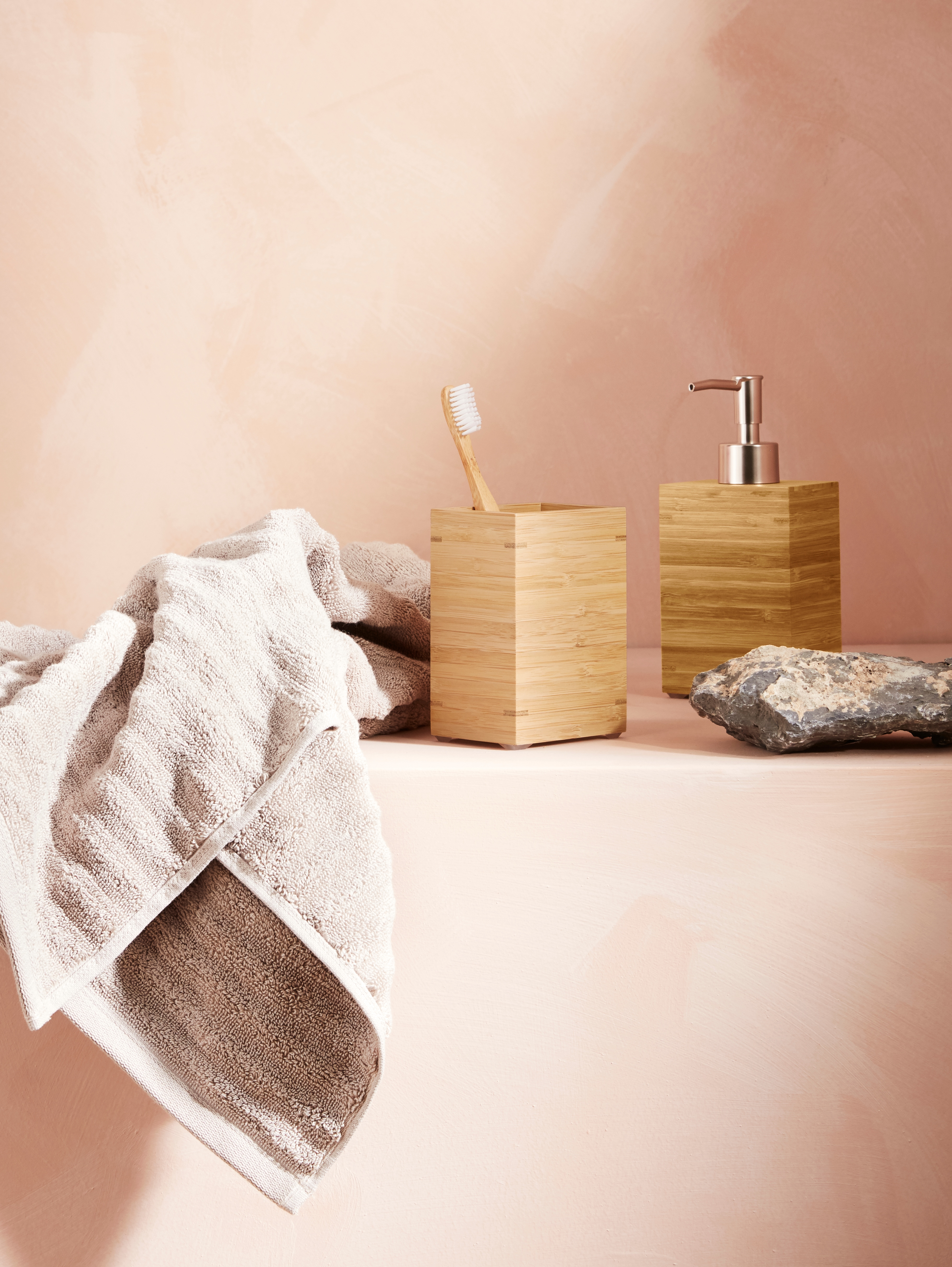 Bathroom with pink wall, boxy bamboo toothbrush holder and bamboo soap dispenser, with beige terrycloth towel.
