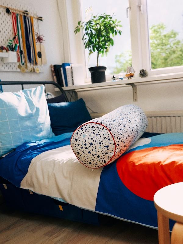 Un dormitor cu un pat KOPARDAL în fața unei ferestre cu o cuvertură BRUNKRISSLA multicoloră și față de pernă și o pernă decorativă MÖJLIGHET.