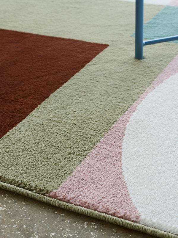 Der weiche Flor des STENMÄTARE Teppichs mit vom Bauhaus inspirierten Muster in Rosa, Mintgrün, Blau und Dunkelrot.