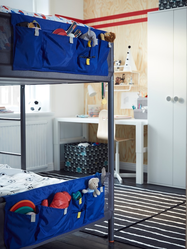A dark grey TUFFING bunk bed with blue MÖJLIGHET bed pockets filled with toys and games stands in a kids' room.