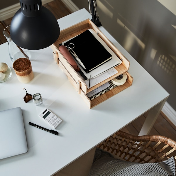 Overhead view of a white desk with a letter tray, a lamp, and a latte.