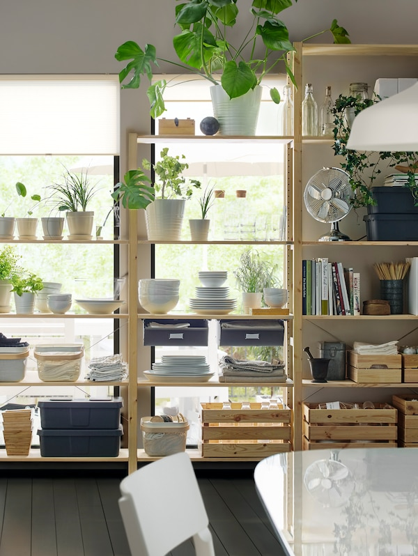 A big solid pine IVAR shelving combination holding boxes, plants and bowls stands against a wall with large windows.