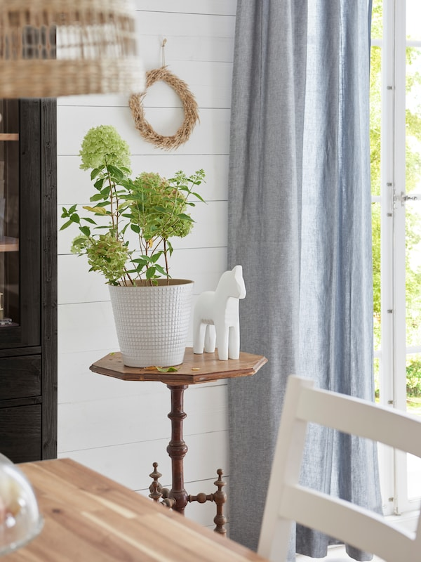 CHIAFRÖN plant pot with green plants, next to a white, decorative horse ornament on a vintage side table.