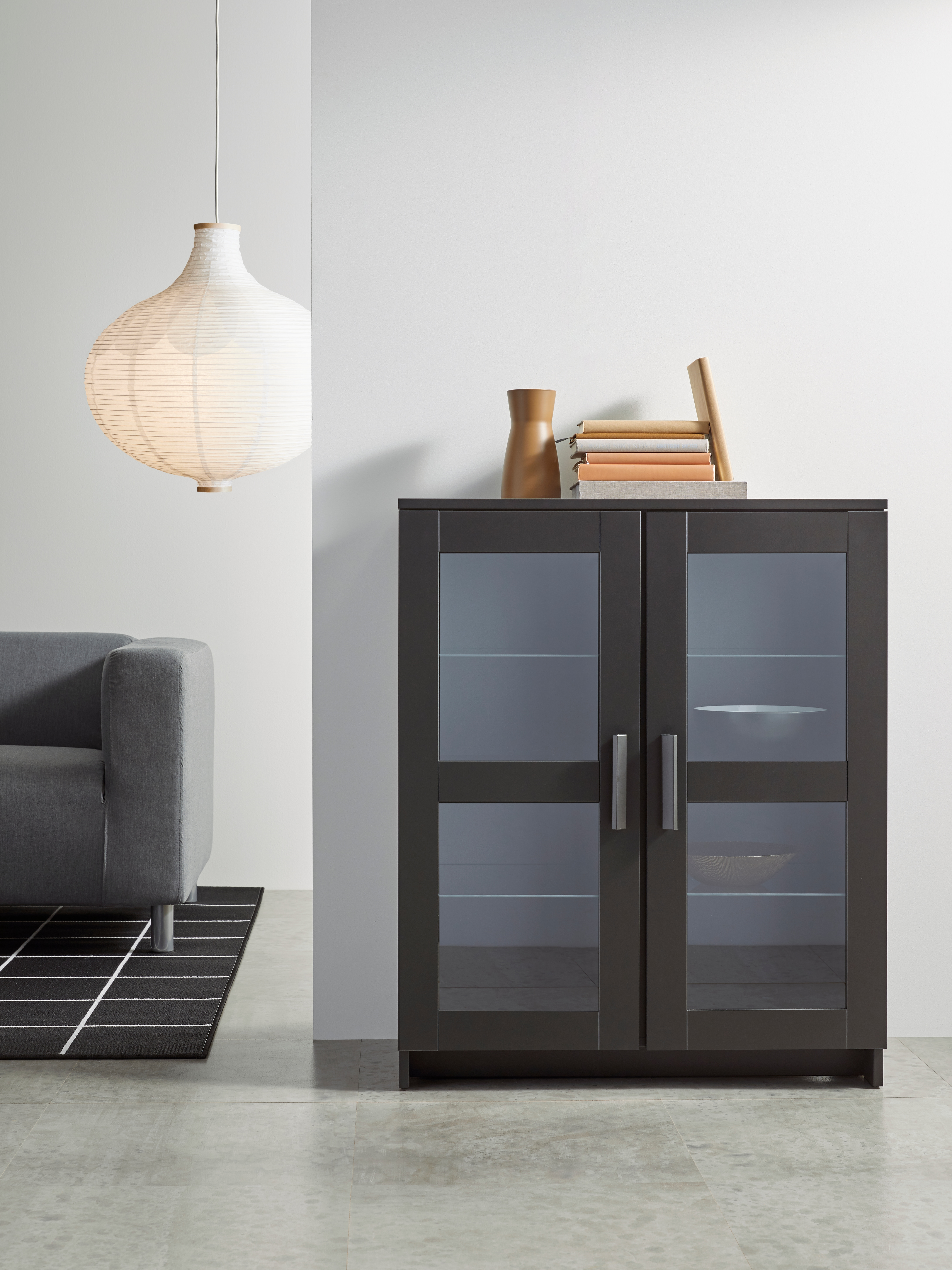 A glass/black BRIMNES cabinet with doors has decorative bowls inside and books on top. It is in a display-style living room.