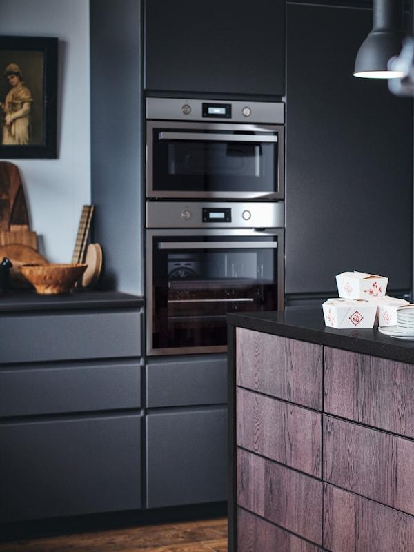 Eine Küche mit VOXTORP Fronten in Dunkelgrau und SINARP Braun. Auf der KARLBY Arbeitsplatte sind Behälter mit mitgenommenen Speisen zu sehen.