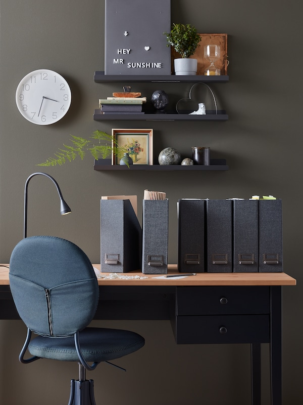 Workspace with desk, chair, dark-grey TJOG magazine files, a TROMMA wall clock and decorations on dark-grey MALMBÄCK shelves.