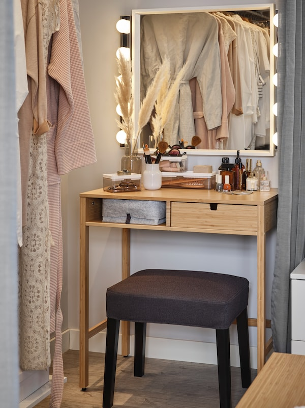 A beauty station where a bamboo NORDKISA dressing table and a SAKARIAS stool sit under a NISSEDAL mirror and two wall lamps.