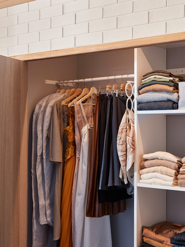 The inside of a fitted AURDAL wardrobe combination with some clothes hanging from rails and other clothes folded on shelves.