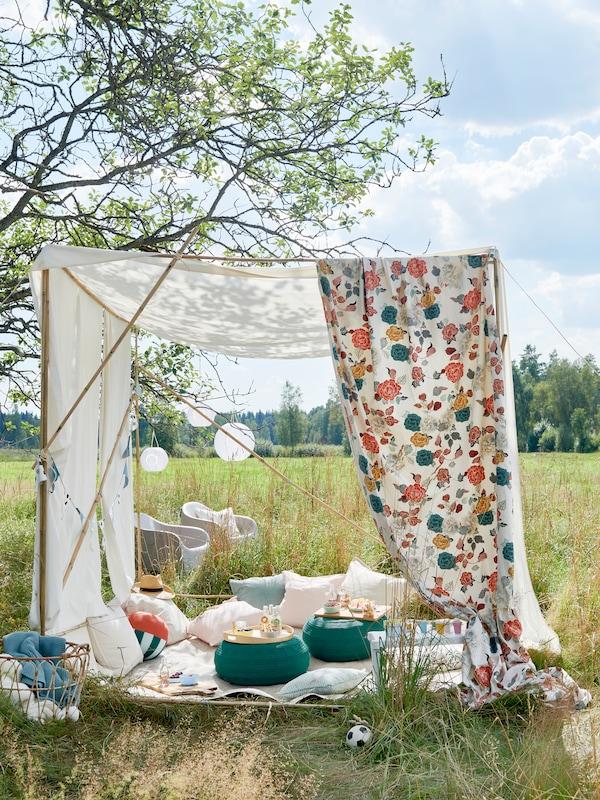 Un abri solaire de fortune composé d'une structure en bois recouverte de textiles blancs et colorés. En dessous, tu peux voir un pique-nique avec des couvertures, des oreillers et de la nourriture.