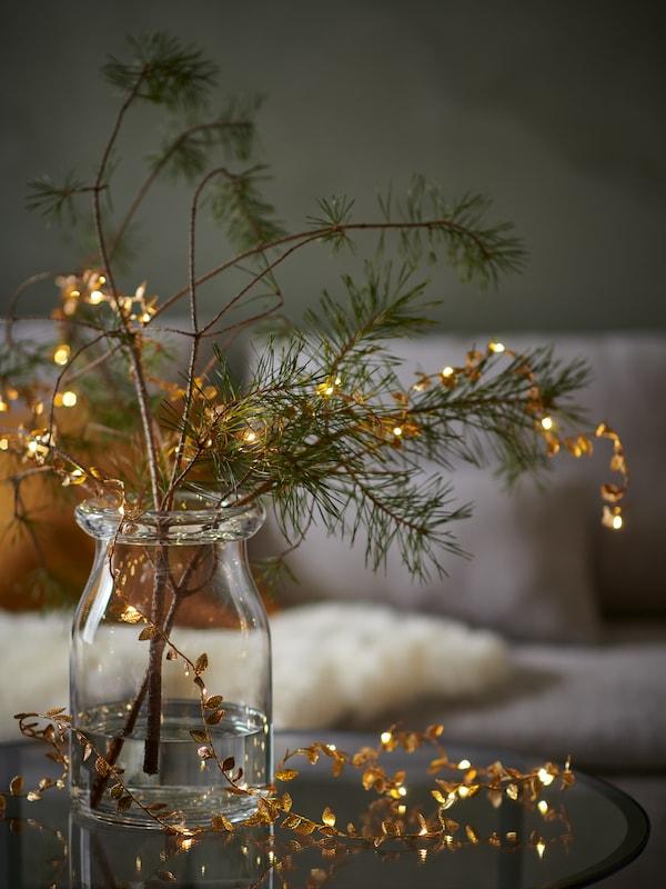Goudkleurig STRÅLA led-lichtsnoer op batterijen in bladvorm in een doorzichtige vaas met decoratieve dennenboomtakken erin in een woonkamer met een bank op de achtergrond.