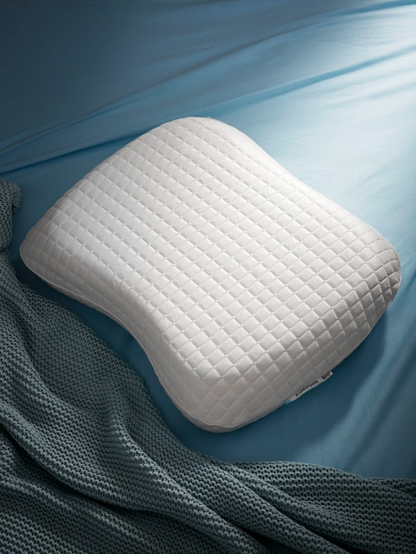 An uncovered KLUBBSPORRE pillow on a bed covered with blue bed linen and a grey-blue blanket.
