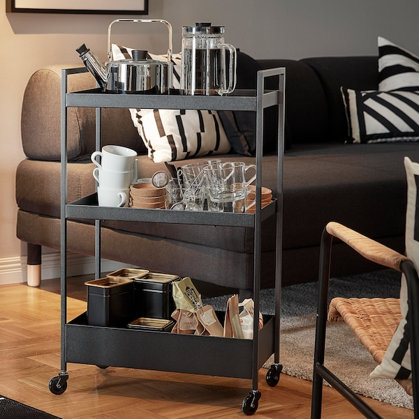 A black NISSAFORS trolley holding coffee pot and tea pot, mugs, cups and other items. Behind is a dark-grey sofa bed.