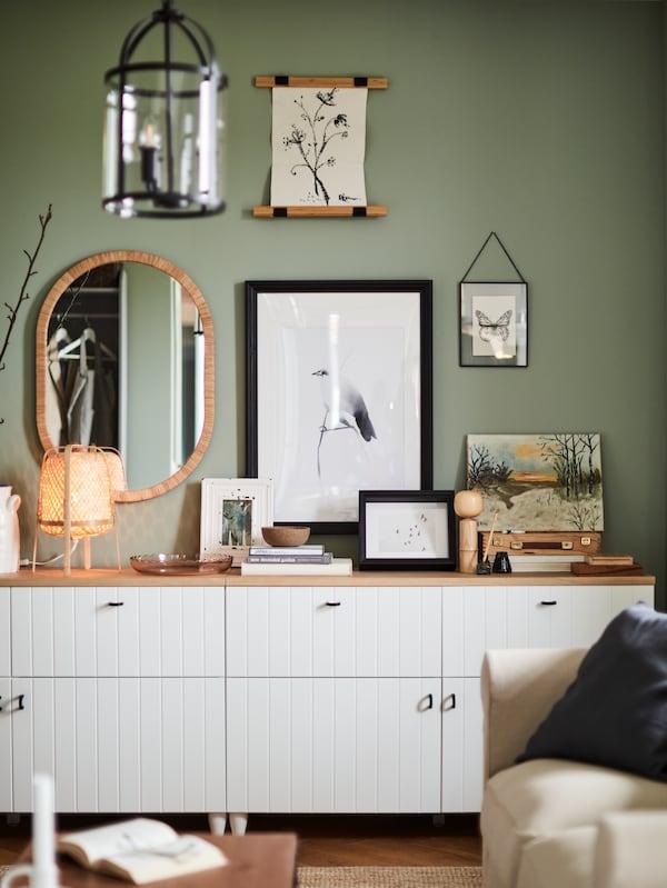 Un perete verde cu desene încadrate ale unei păsări, flori și un fluture, o veioză de bambus, o oglindă, un corp alb.