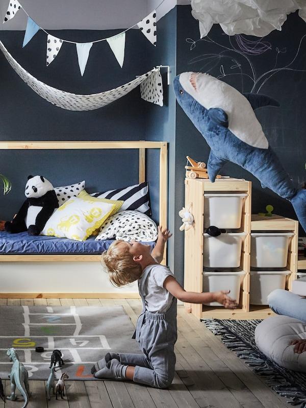 KURA 쿠라 침대를 놓은 블루 톤의 침실에서 HEMMAHOS 헴마호스 러그 위에 무릎을 꿇고 앉아 BLÅHAJ 블로하이 봉제인형을 가지고 노는 아이.