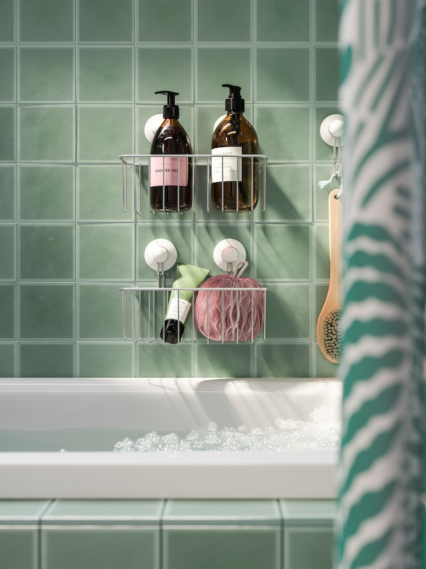 Shower gels and other shower items stored in baskets with suction cups that are attached on a tile wall over a bathtub.