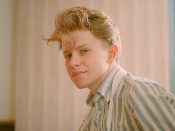 Flynn McGarry amerikai séf zöld-fehér csíkos ingben ül, és a kamerába néz.