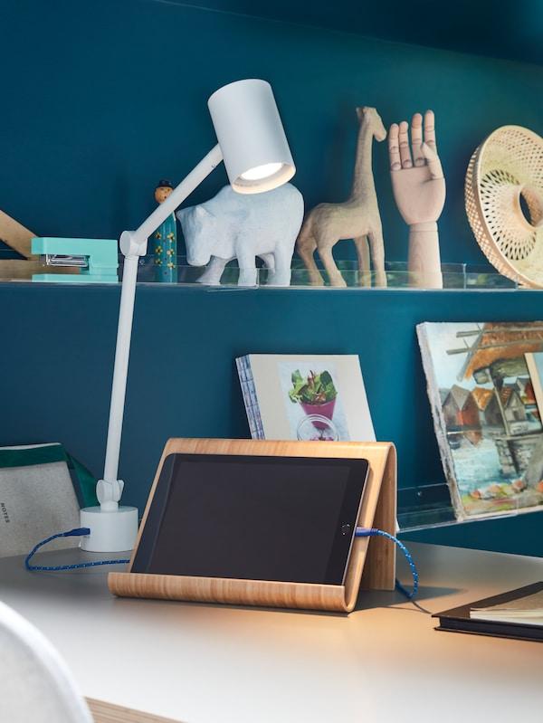 Biela pracovná/nástenná lampa NYMĹNE osvetľuje stojan s tabletom z bambusovej dyhy VIVALLA na bielom stole.