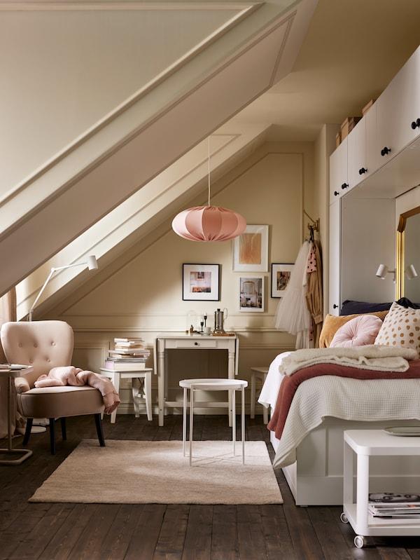 Egy világos szoba egy kanapéággyal, fehér gardróbokkal, egy fehér GLADOM tálca-asztal egy bézs szőnyegen, bézs fotel és rózsaszín függőlámpa.