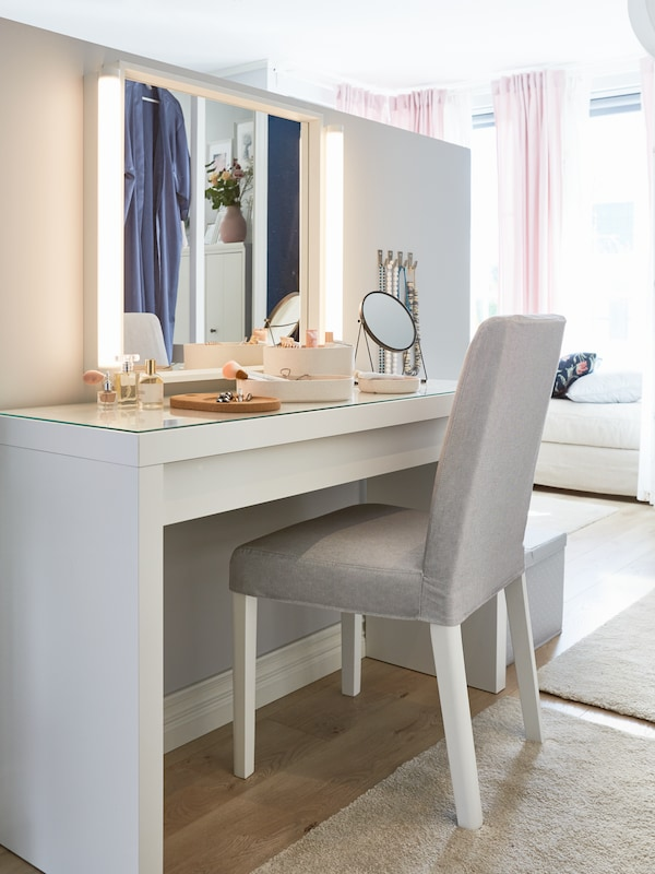 A white MALM dressing table filled with various make-up items under a large vanity mirror with lights.