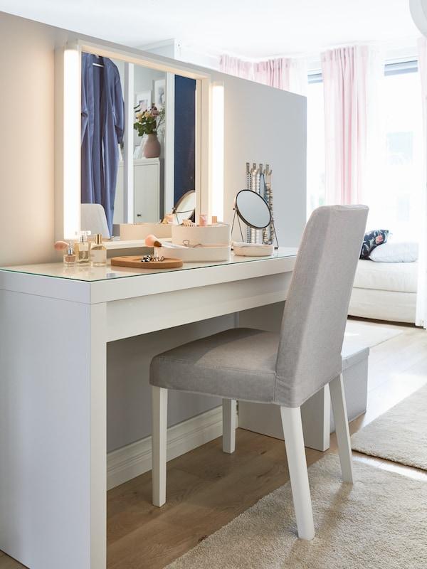 Vitt MALM toalettbord med olika sminkgrejer står under en stor sminkspegel med lampor.